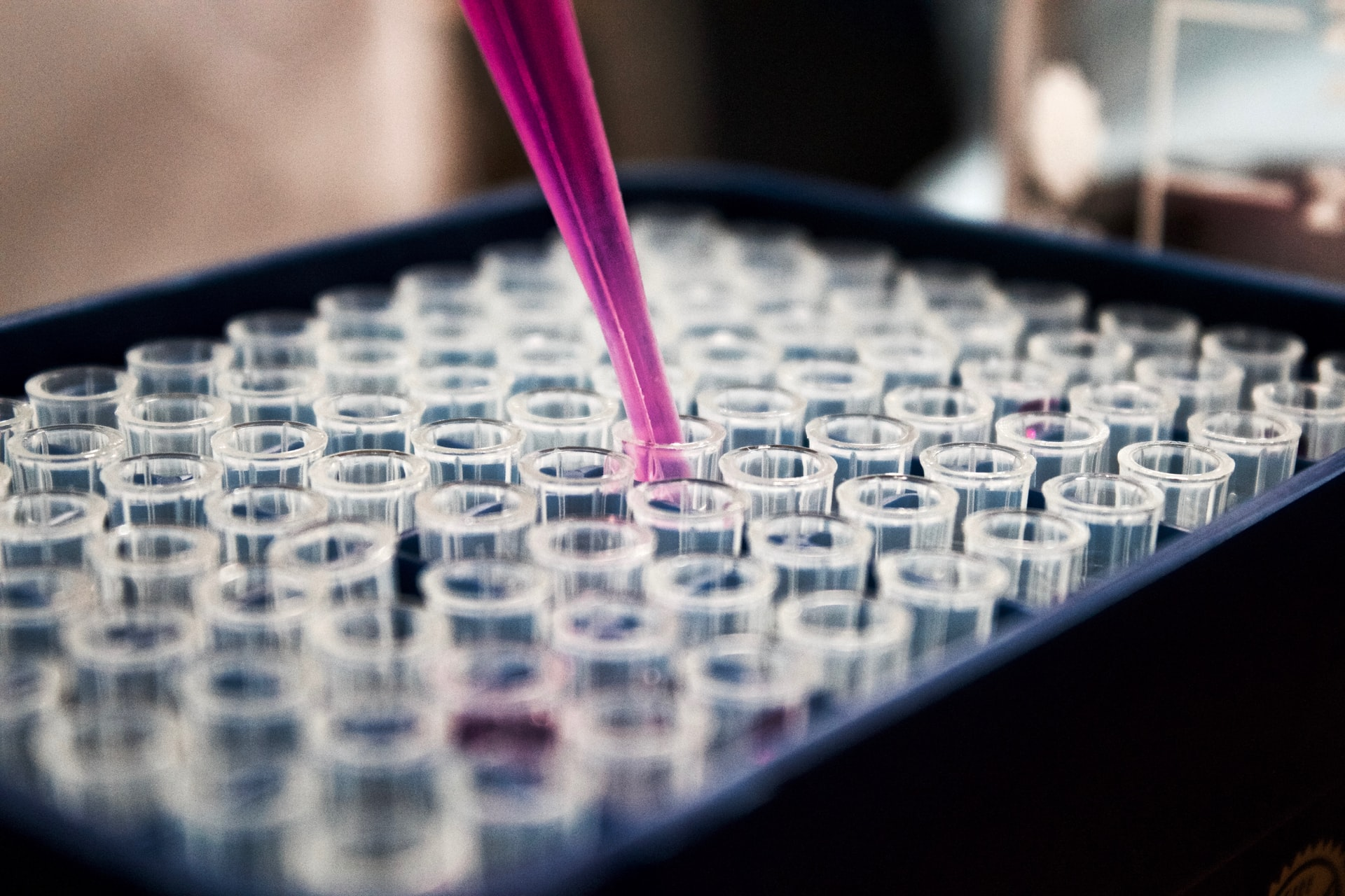 This image is taken at a lab with small amounts of solution being dropped into test tubes.