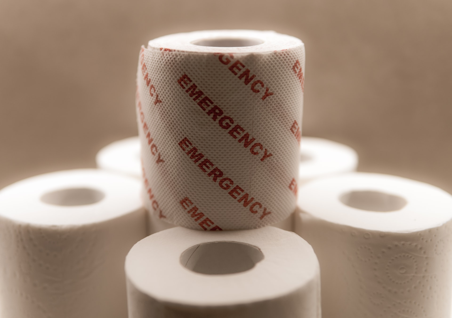 Here we see rolls of toilet paper with one stacked up reading 'emergency'