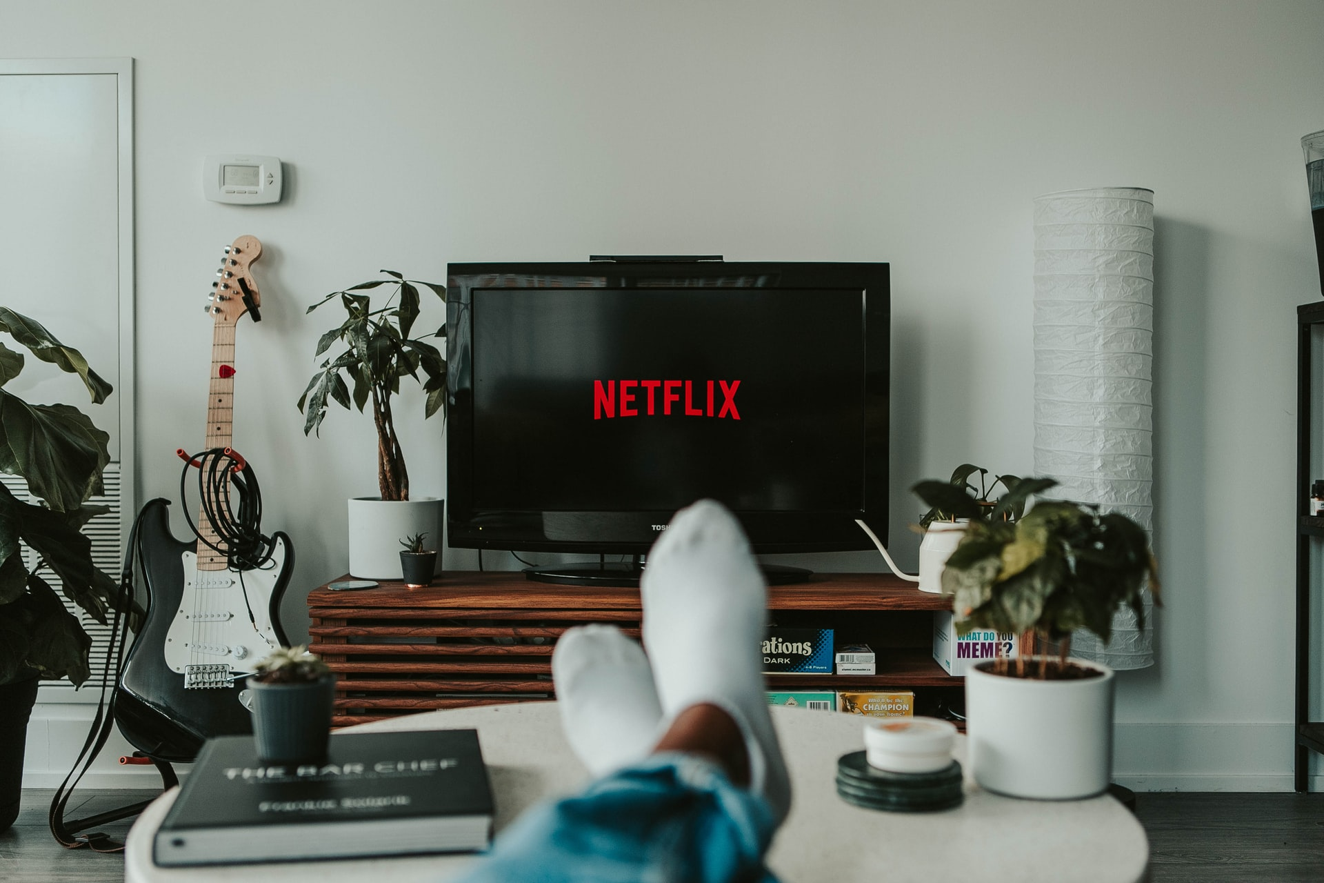 This image shows feet up on a coffee table with Netflix playing in the background.