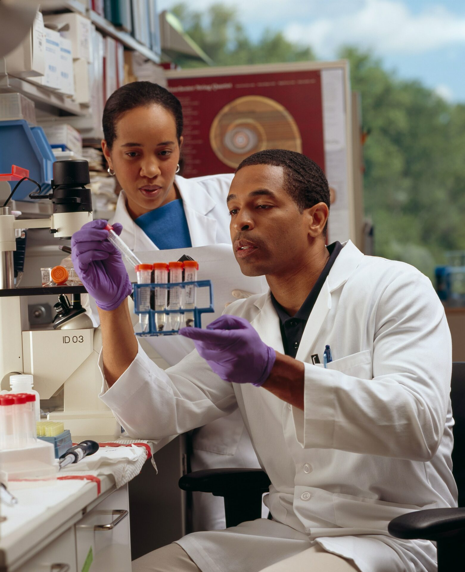 Two scientists look at a test in a lab for the national cancer institute.