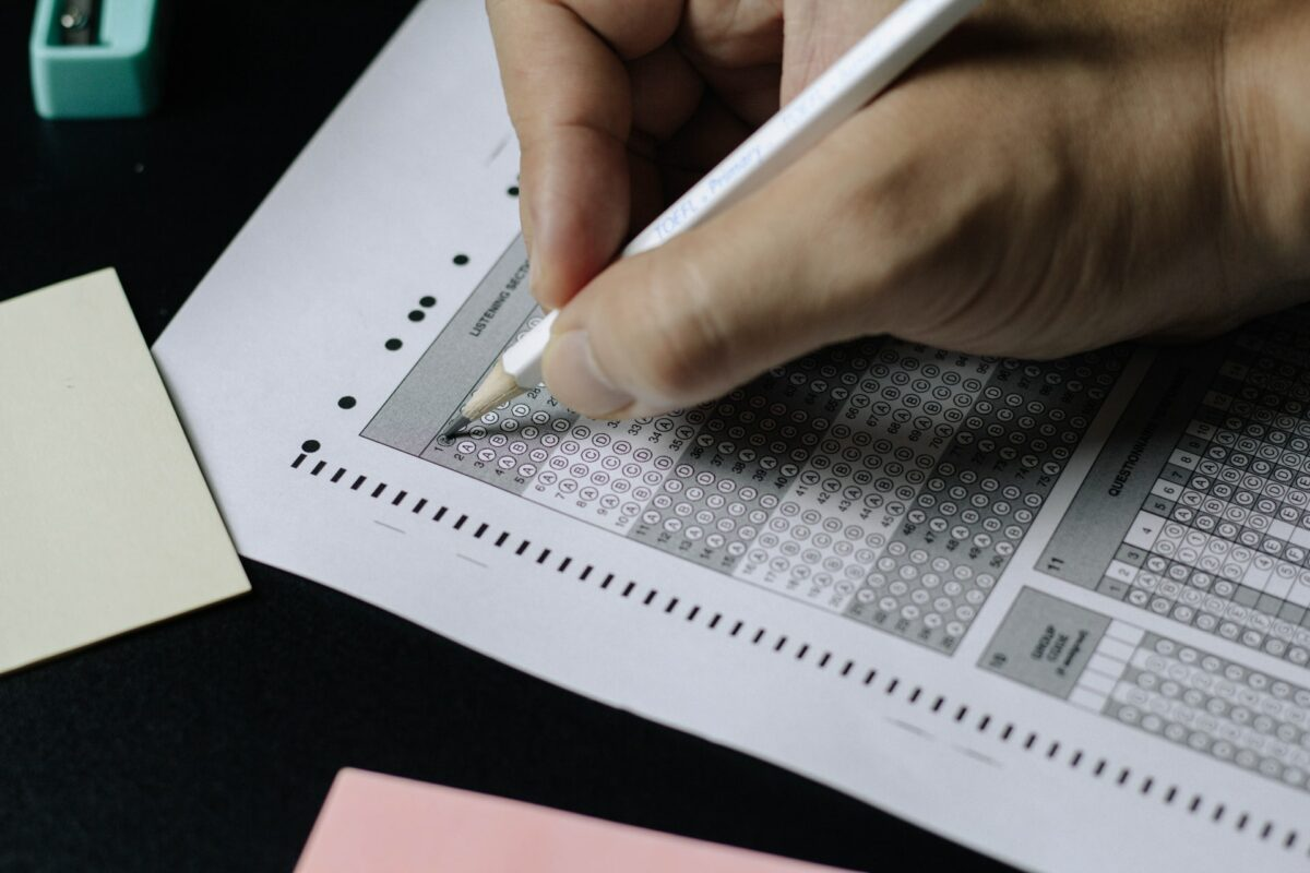 This image shows a hand holding a pencil completing an exam that is tick-box based.