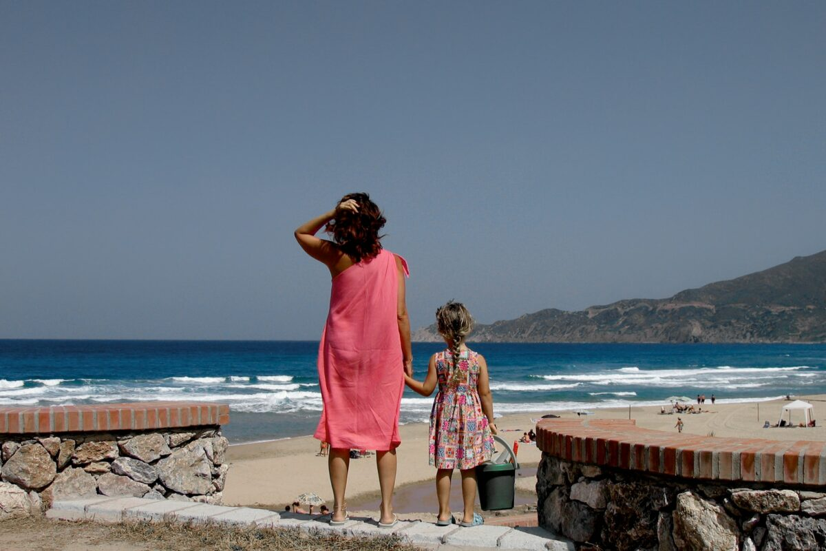 This image shows a mother and daughter hand in hand at the beach