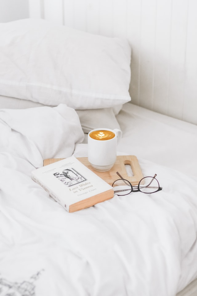 A bed that has scrunched white sheets. To one side is a pair of glasses, a novel and a mug of coffee on top of a small wooden chopping board.