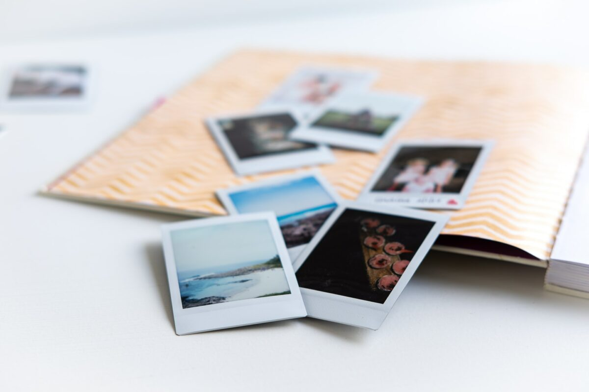 This image shows a scrapbook with seven polaroids of the beach/seaside coming out of the book.