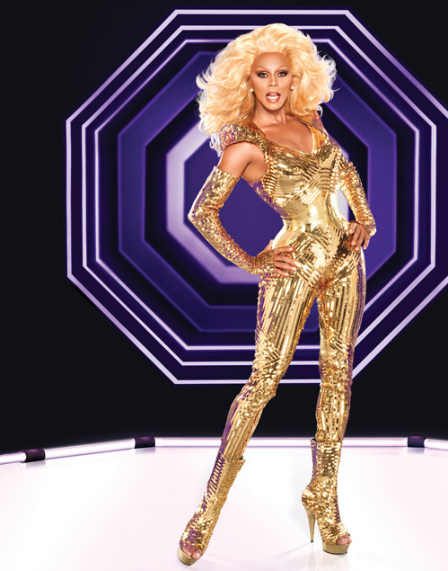 RuPaul is pictured here in the early 2010's in a gold one piece. He is in drag with a large blonde wig.