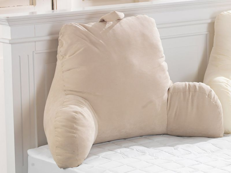 This shows a light pink luxury suade backsupport pillow leaning on a white bed frame.