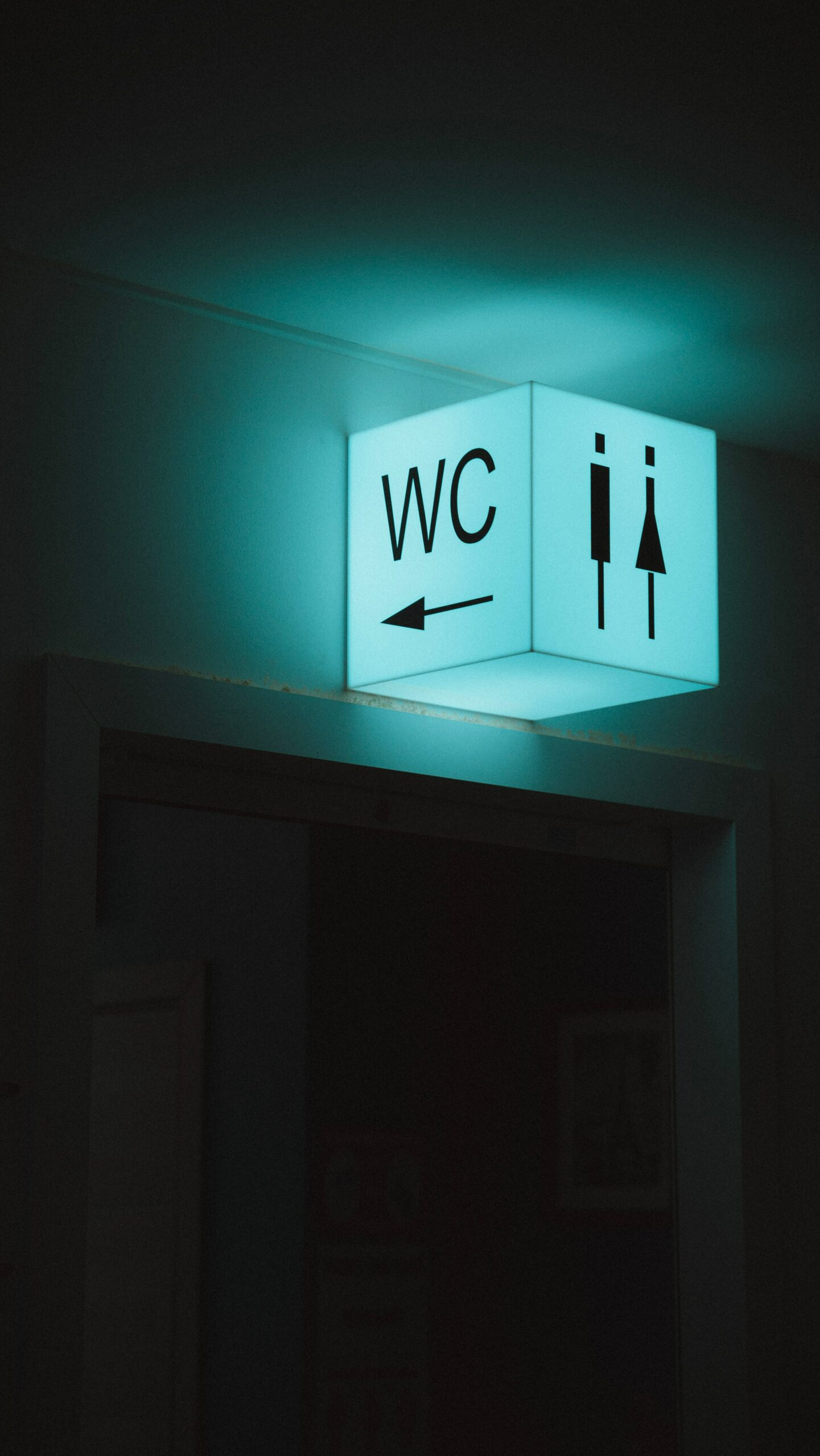This is a dark image with a light cube with LEDs reading wc.