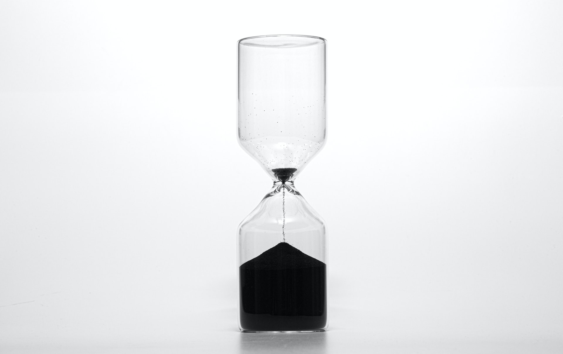 This image shows a sand timer on a white background. The sand is black creating a B&W contrast.
