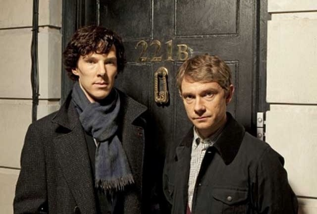 This images was taken during the first episode of Sherlock Holmes. Both the main characters are wearing black coats and staring neutrally at the camera. They are stood in front of a black door that is numbered '221B'.