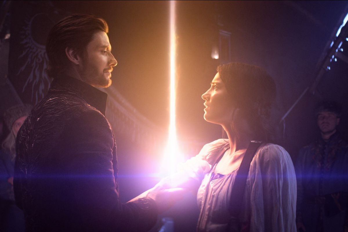 In this image, the Darkling and Alina are facing each other. The Darkling has hold of Alina's arm and her power is shooting out of a cut on her arm.