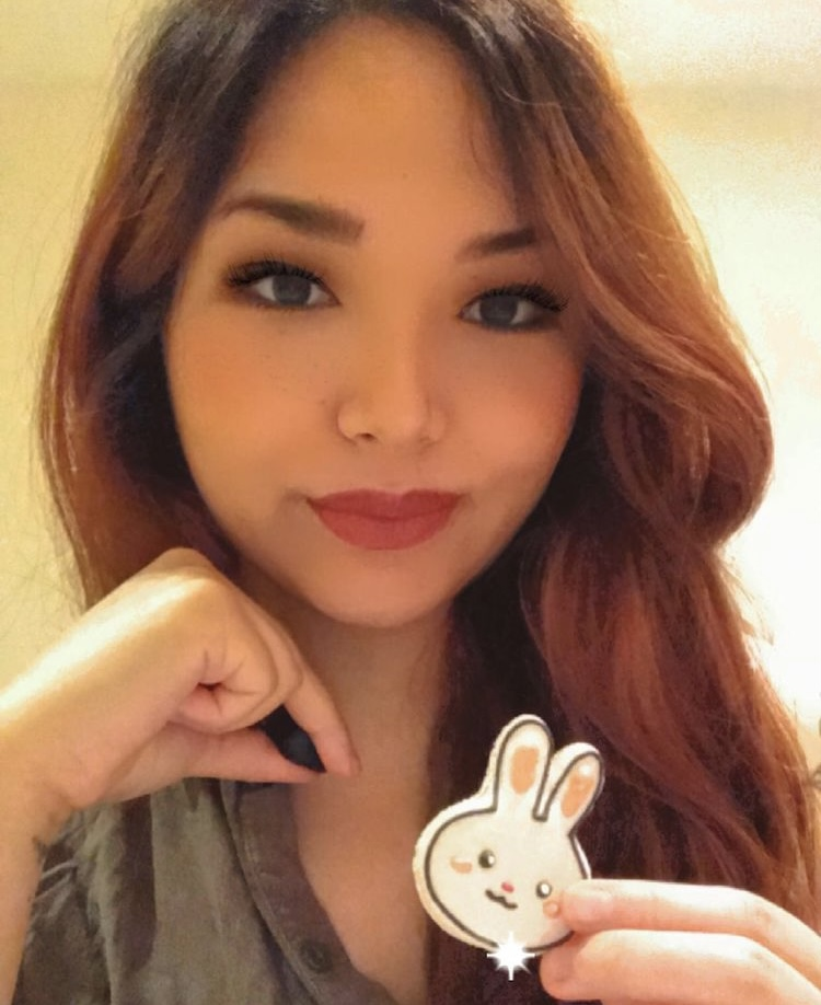 In this photo. Arisa is smiling at the camera and holding one of her Easter macarons.