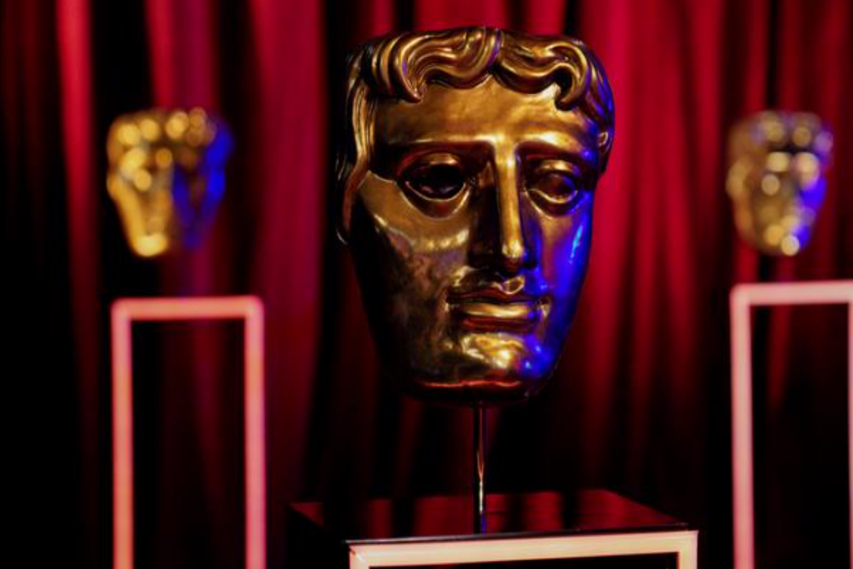 """This image shows the award that is given to winners of the awards ceremony, the """"BAFTAs"""". There is one award at the front centre of the image that is focused and two behind that are out of focus. They have been placed on podiums in front of a red curtain."""
