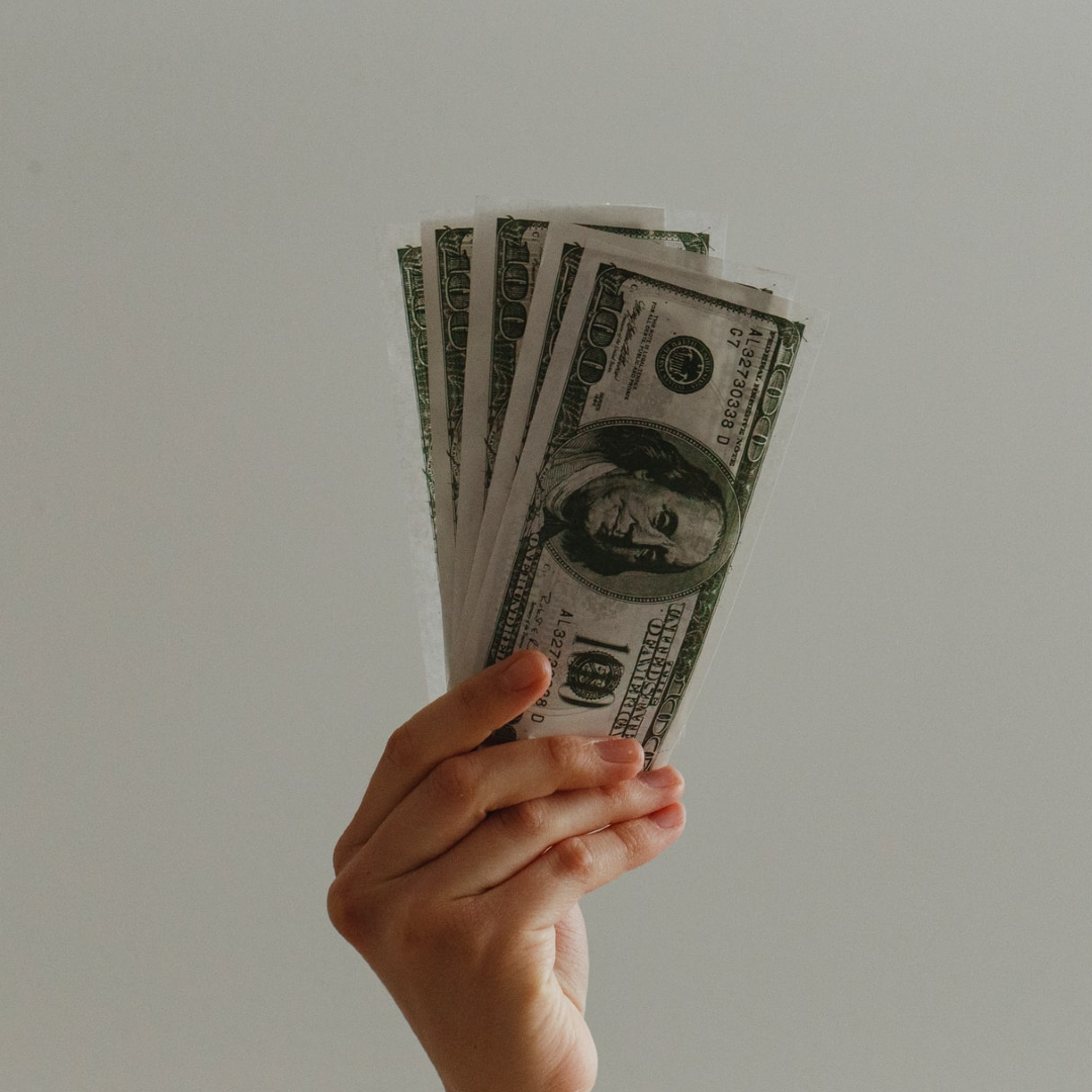 This image is of a hand holding up american dollars.