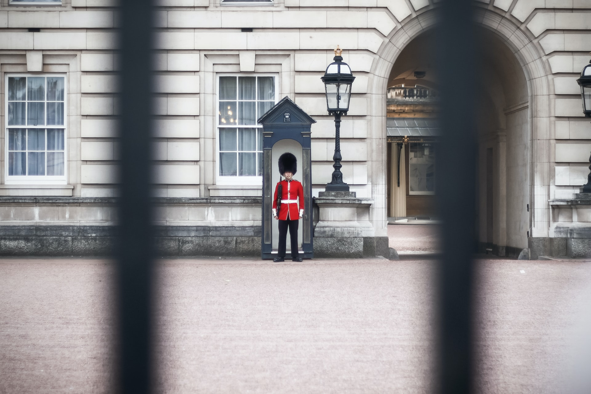 The picture shows a Royal Guard standing at their post, guarding Buckingham Palace.
