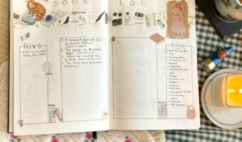 In Megan's image, a notebook is wide open displaying a book log. the page is decorated with stickers and drawings of books. Surrounding the notebook is a lit candle, a cup of tea and washi tape.