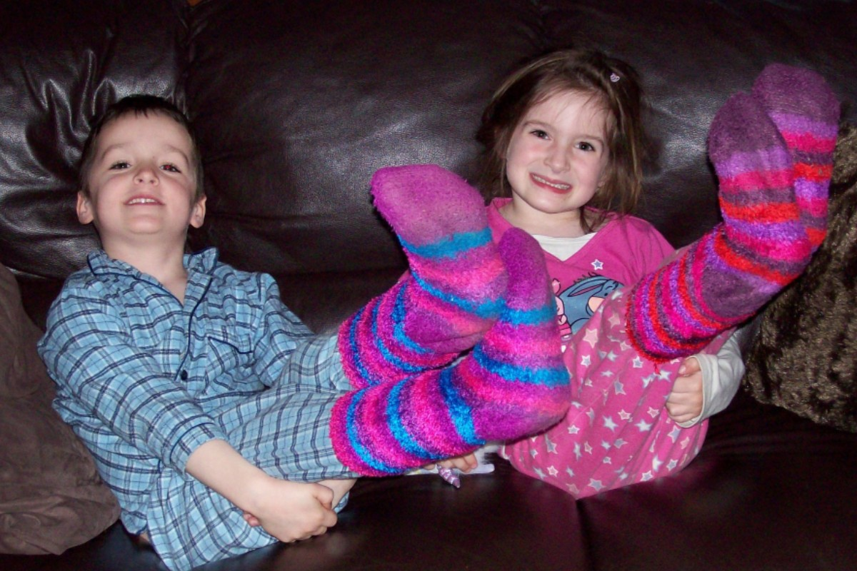 This is a photo of Max and Hope when they were younger. Both are sat on a black sofa, wearing pyjamas and fluffy bed socks. Both are raising their feet in the air to highlight the fact they are wearing bed socks.