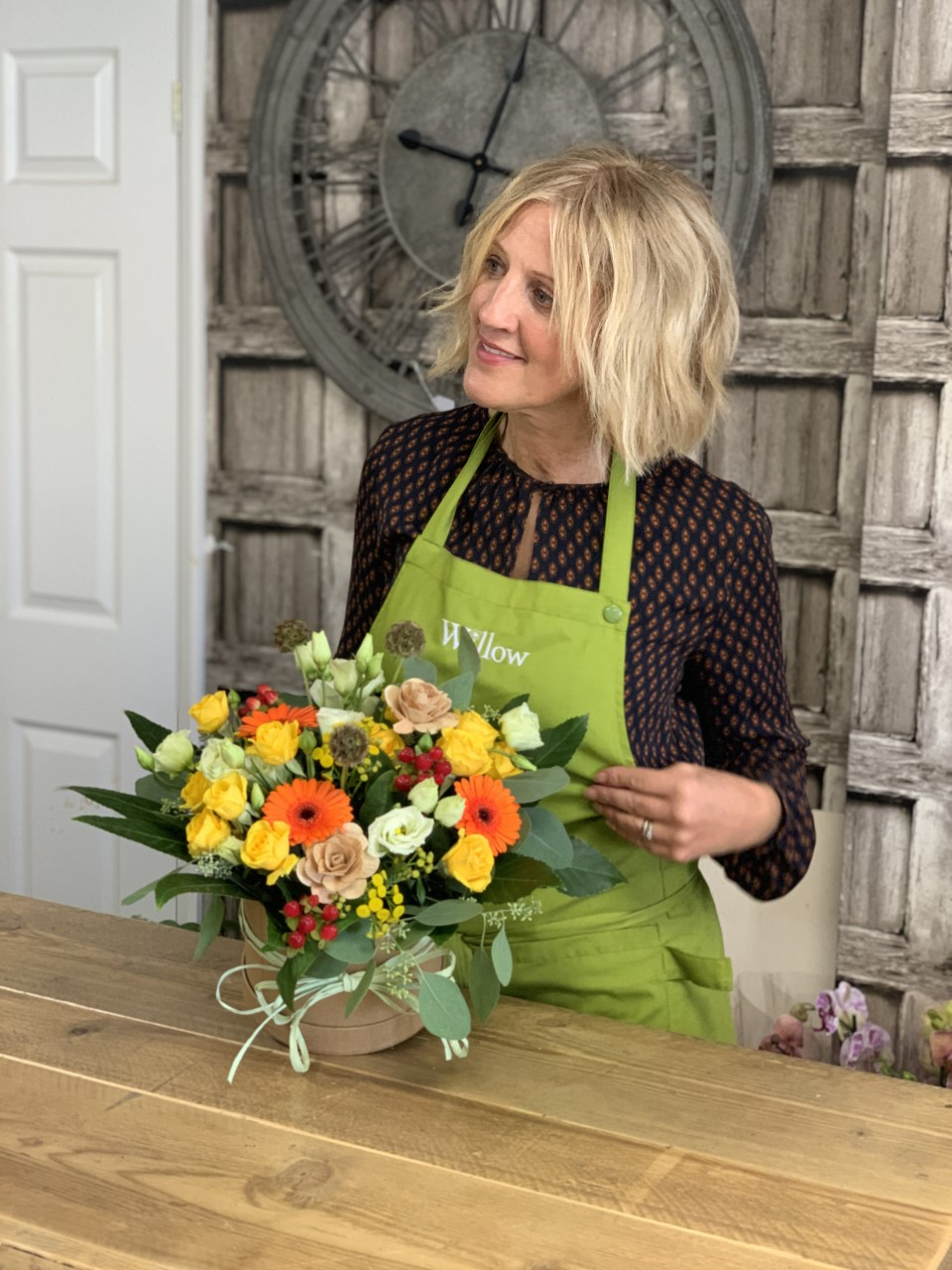 In this image, Diane is wearing a green apron and is tending to a bouquet full of white, orange and yellow flowers.