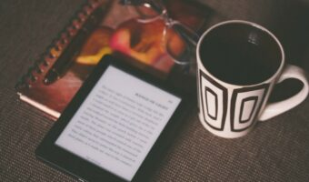 An electronic reading device is sat on a table on top of a notepad, a pen and next to a white mug. The device is turned on and the user is reading something.