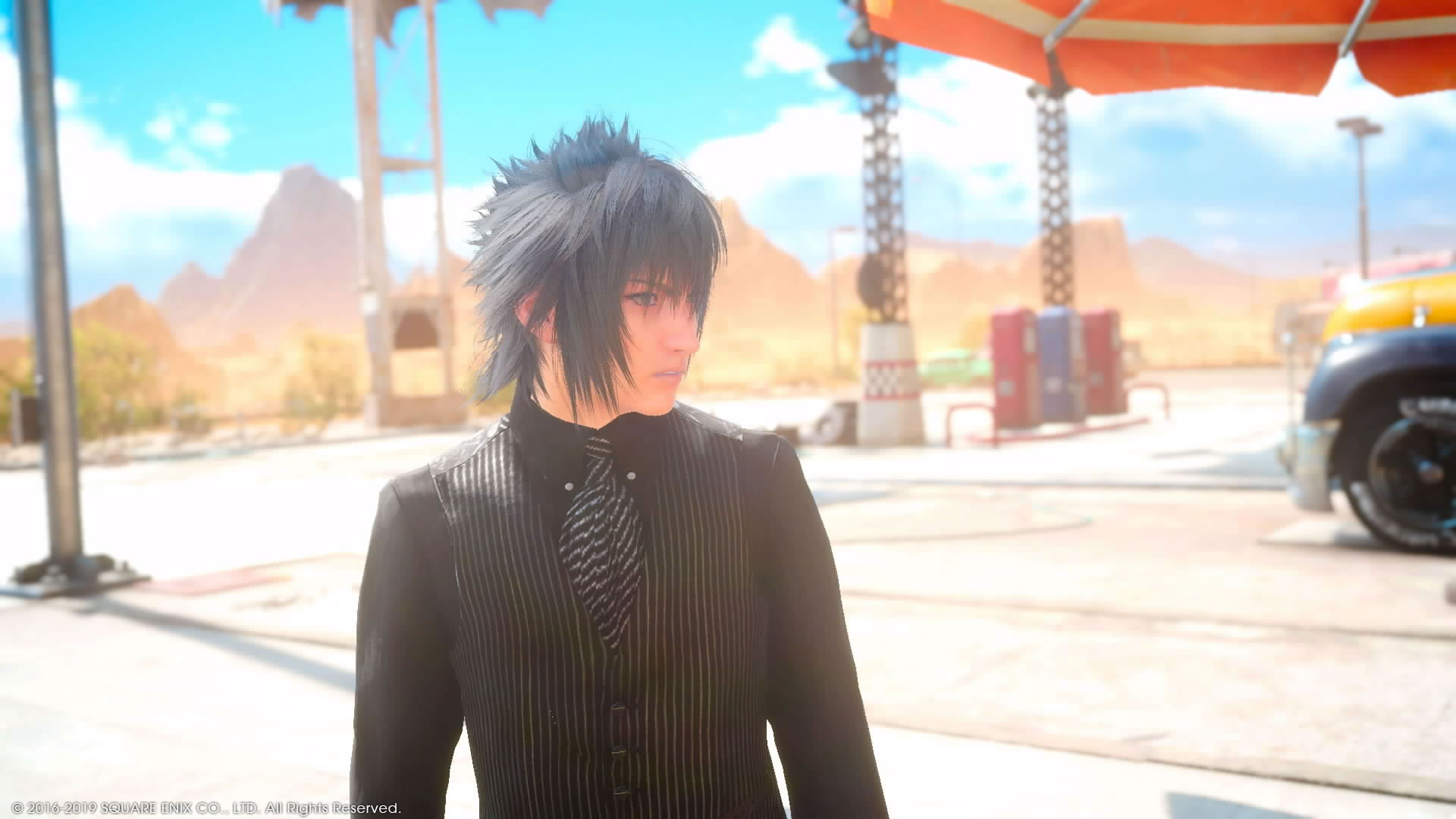 In this image, a game character, a male with dark hair and dressed in a black suit, is looking off screen to the right.