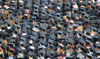 This image shows a birds eye view of many graduates standing together.