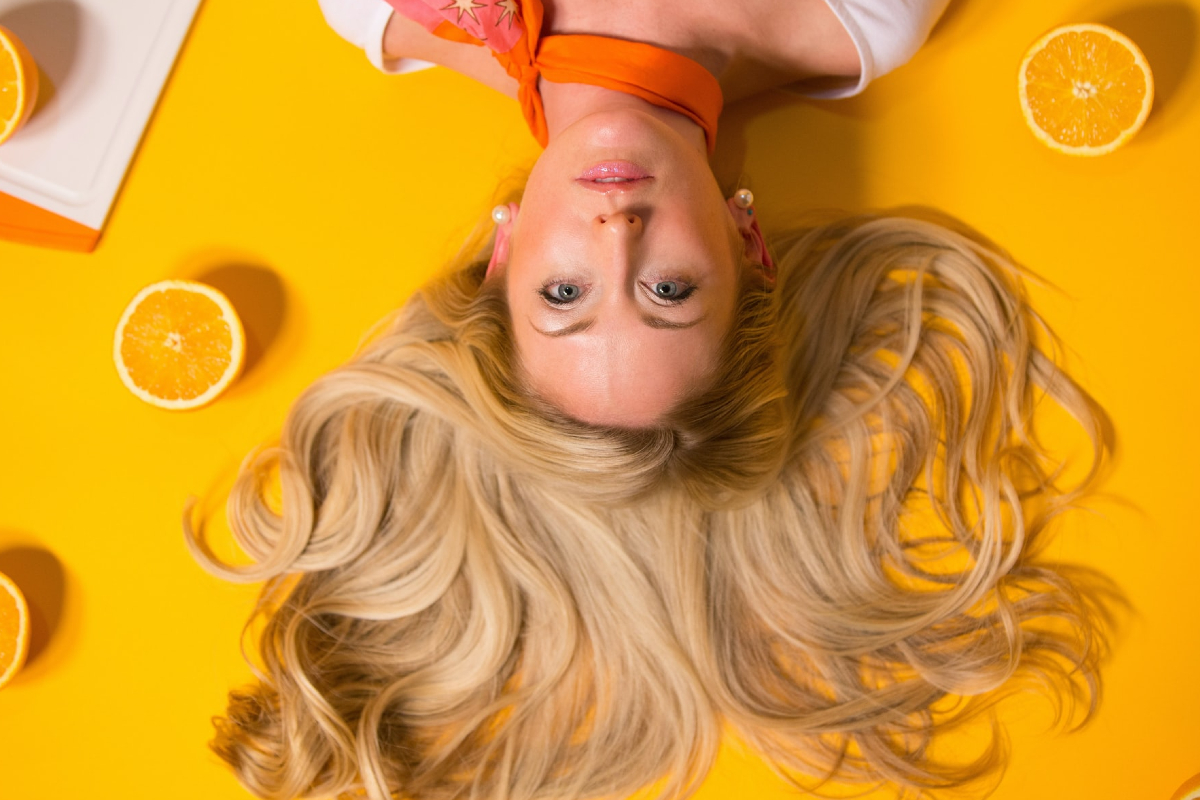 This image shows a blonde lady laying down displaying her hair on an orange background with citrus fruits surrounding her.