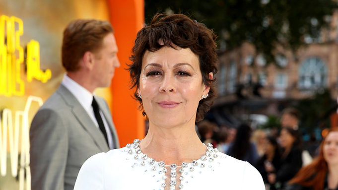 In this image, Helen McCrory is stood posing for a photo, wearing a white embellished dress. Behind her is her husband, Damian Lewis, wearing a grey suit.