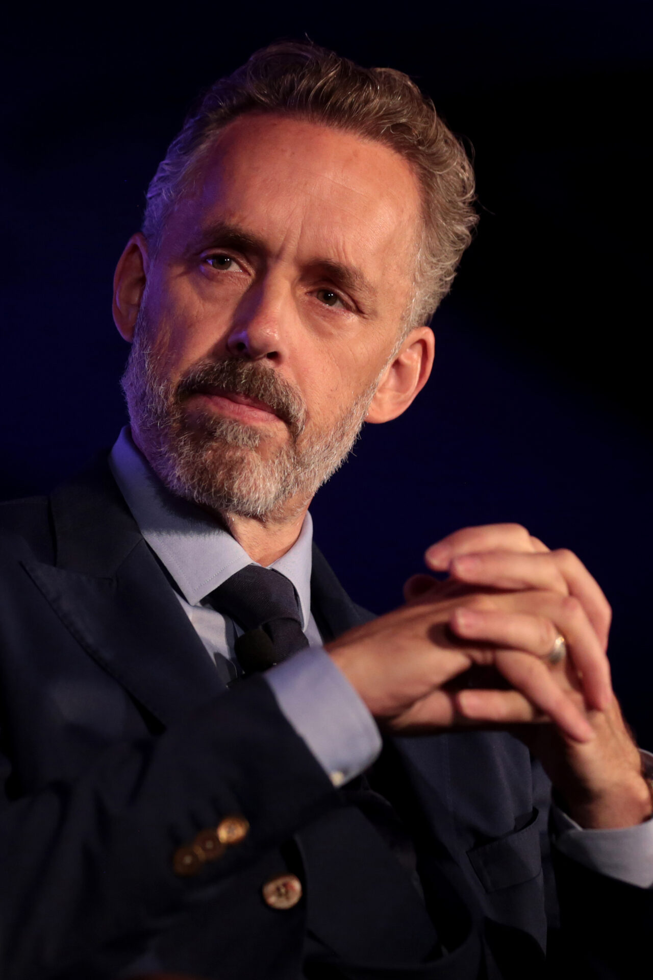 Jordan Peterson is pictured here locking his hands as he looks out to the left of the camera on a dark stage. His face is partly shadowed. Peterson is wearing a black suit and tie.