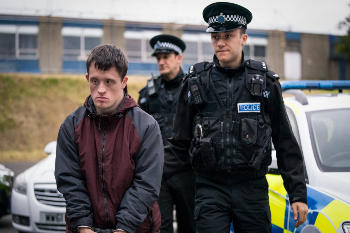 This image shows characters from the BBC programme 'Line of Duty'. The man on the right is wearing a police uniform and the guy on the left is wearing a red and grey jacket.