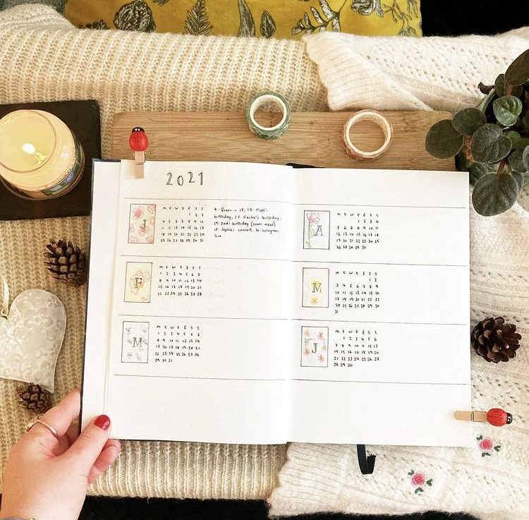 In Megan's image, there is a notebook wide open and it shows a hand drawn calendar up to the month June. Surrounding the notebook are some pine cones, a heart wall hanging, a plant and a lit candle.
