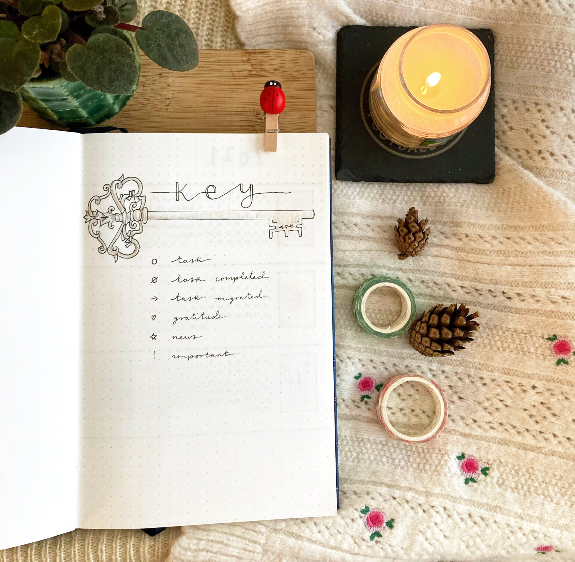 In Megan's image, there is a lit candle, two rolls of washi tape and two pine cones. There is also a square-lined notebook open. On that page is the word 'Key' and a hand drawn key underneath. Under the drawing, there is a key.