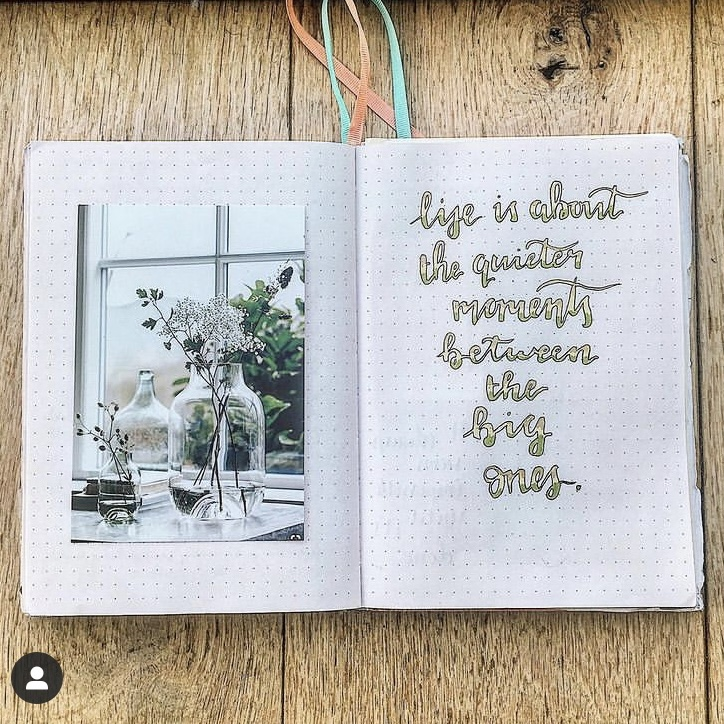 In Megan's image, a notebook is displayed wide open. One page has an images glued in of some flowers in a glass, and the other has a quote written down. The quote is written in cursive bubble writing.