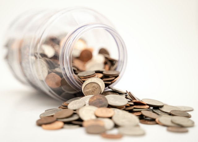 A transparent jar is turned on its side and a variety of different coins are spilling from the jar.
