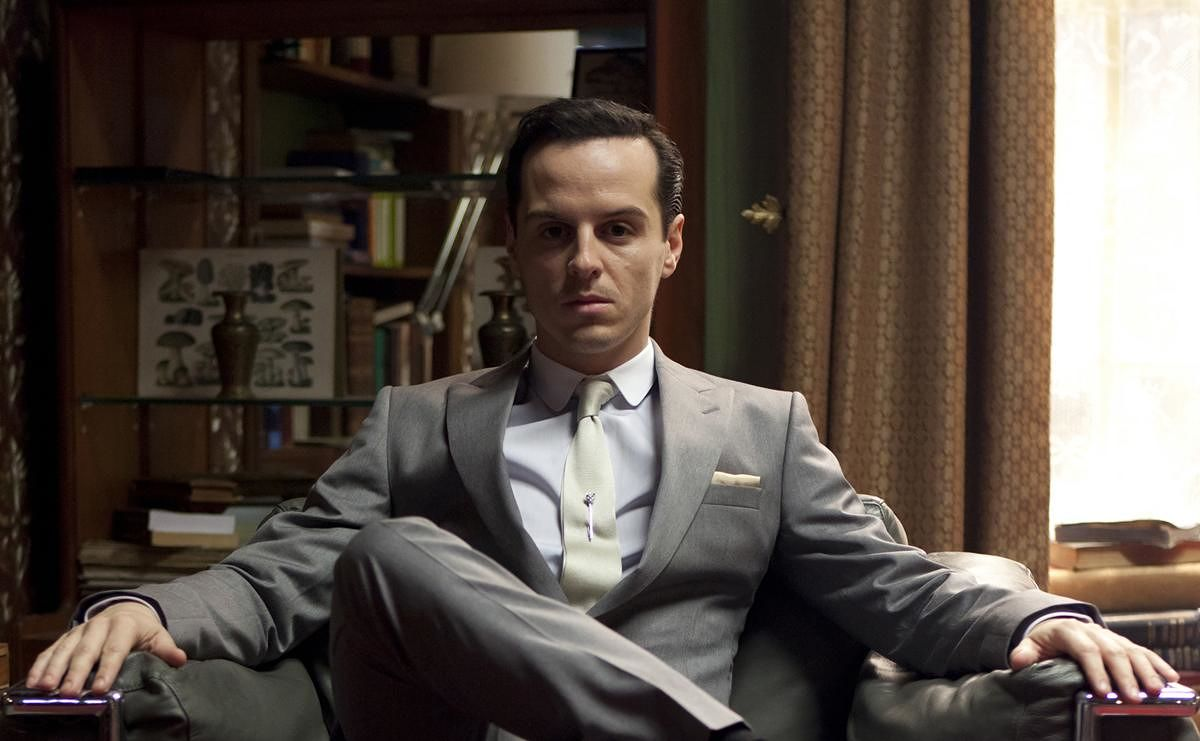 This images shows the main villain of the TV show, Sherlock, sitting in a chair. His right leg is crossed over his left and both his arms rest on the arms of the chair. He is wearing a grey suit with a cream tie and white shirt.