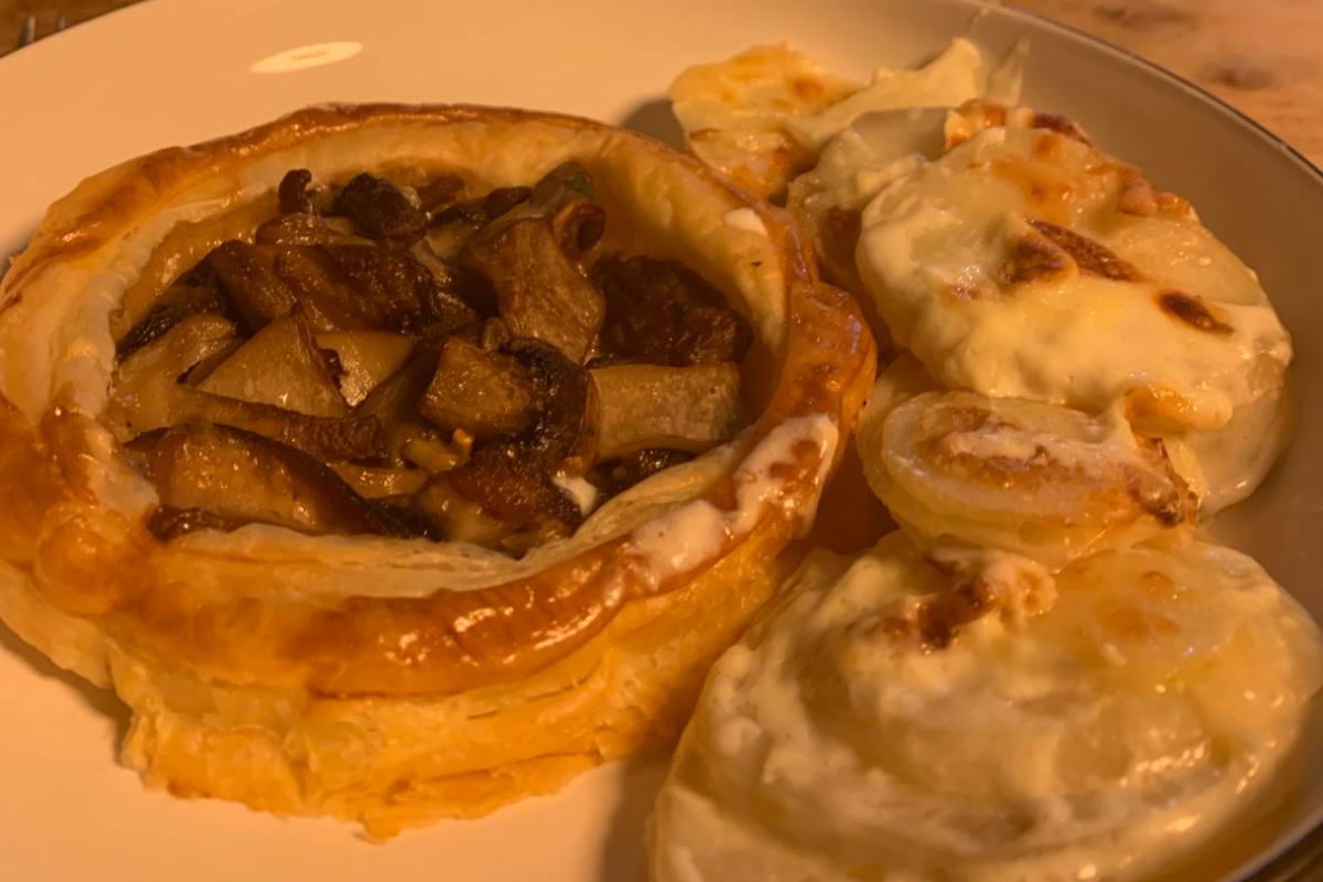 This image shows a Mushroom tart on a plate with dauphinoise potatoes.