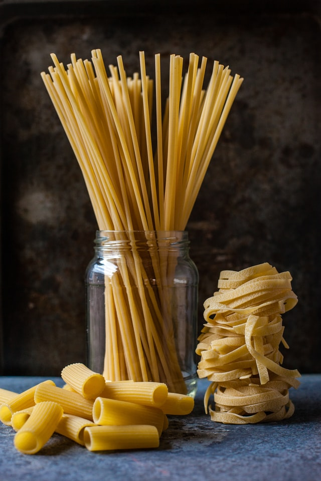 In the image, there is some uncooked spaghetti in a jar, some rolled up tagliatelle next to the jar, and in front of the jar are a few pieces of rigatoni.