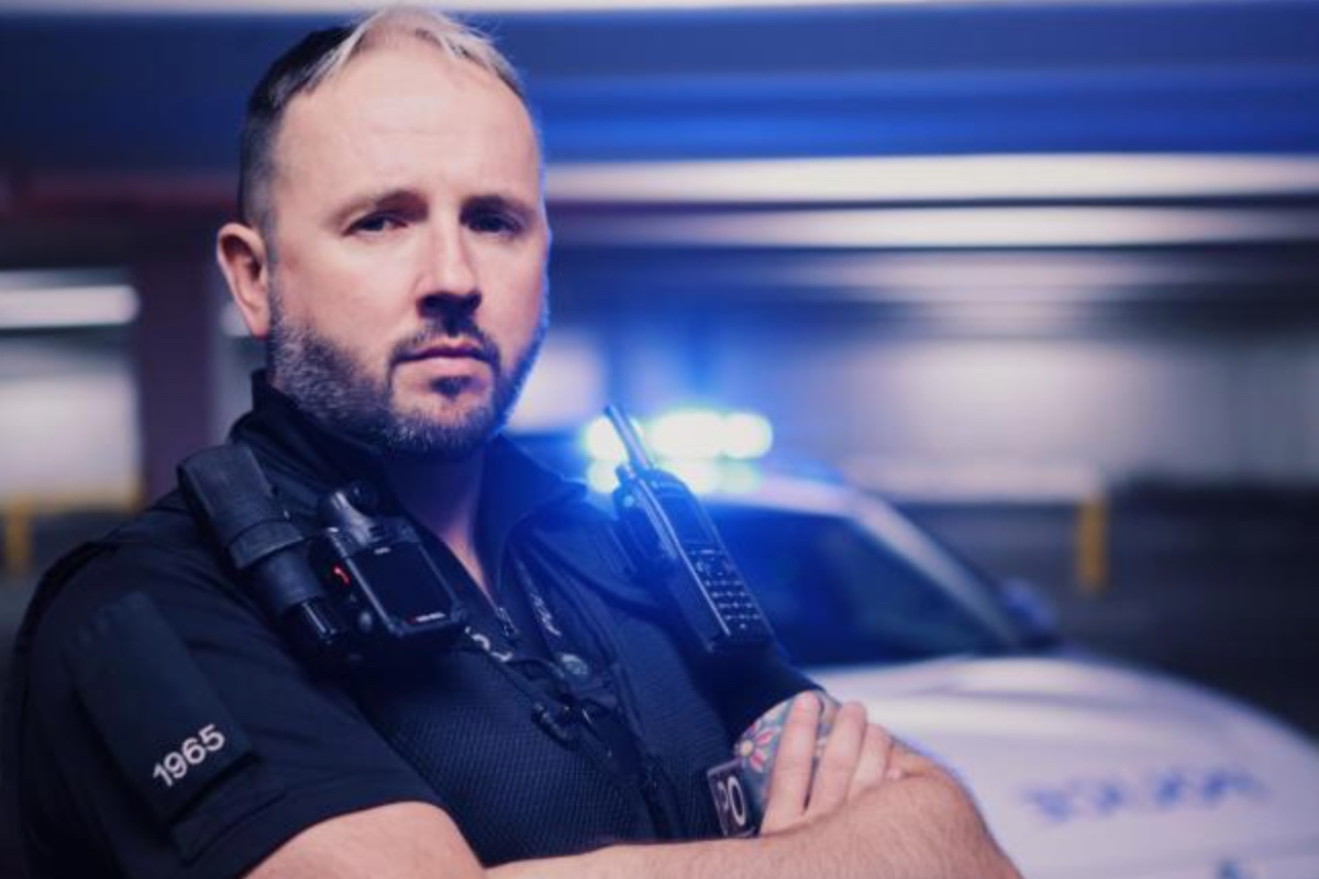 This image shows a police interceptor, Ben. He is wearing a full police uniform, looking at the camera with his arms crossed. In the background, there is a cop car with the blue flashing lights on.