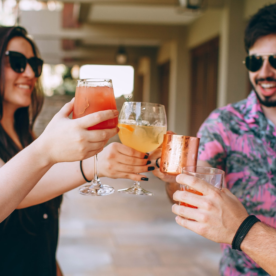 This image shows 4 drinks 'cheersing' with alcoholic beverages.
