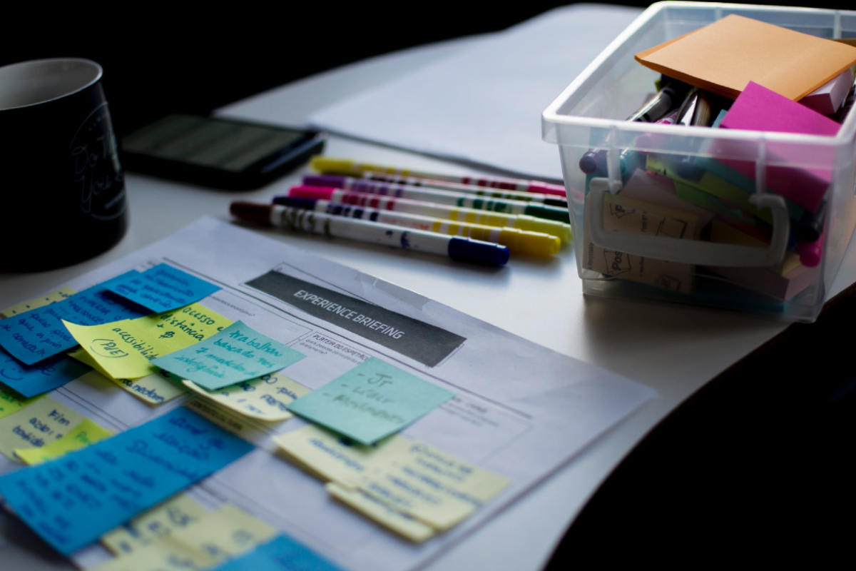 This image shows a selection of felt tip pens and post it notes on a desk.