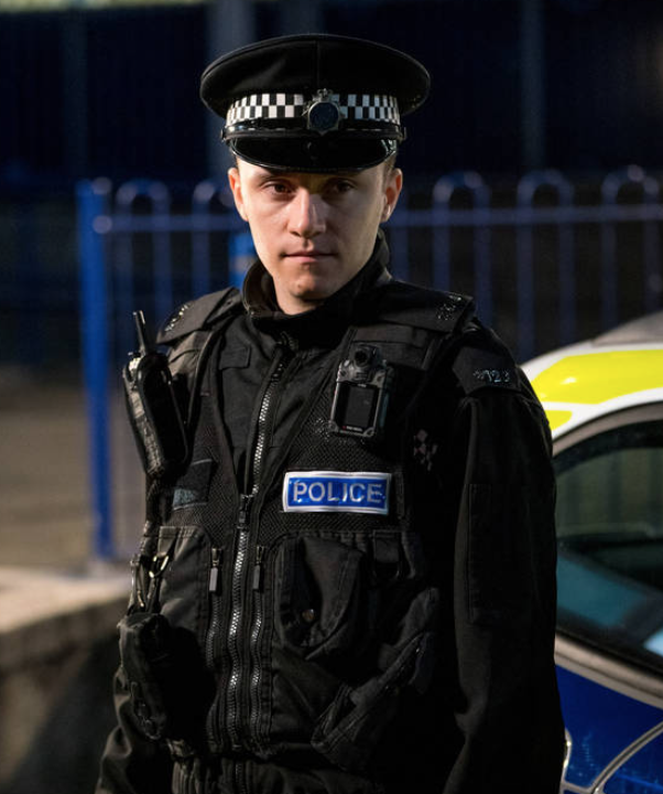 This image shows the character 'Ryan Pilkington' from the BBC show 'Line of Duty'. He is wearing a police uniform and stood in front of a police car.