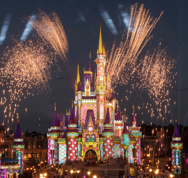 This image shows the Disney castle lit up in a multitude of colours and patterns. They are hosting a fireworks display.