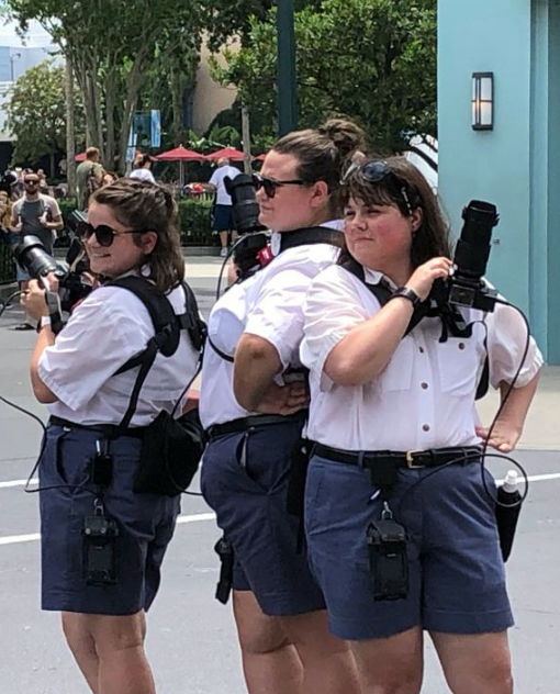 This image shows three women  stood shoulder to shoulder with each other. They are all photographers.