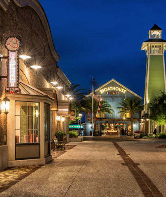 This image shows Disney Springs. There are a few shops that are present and they are lit up due the sky being dark.
