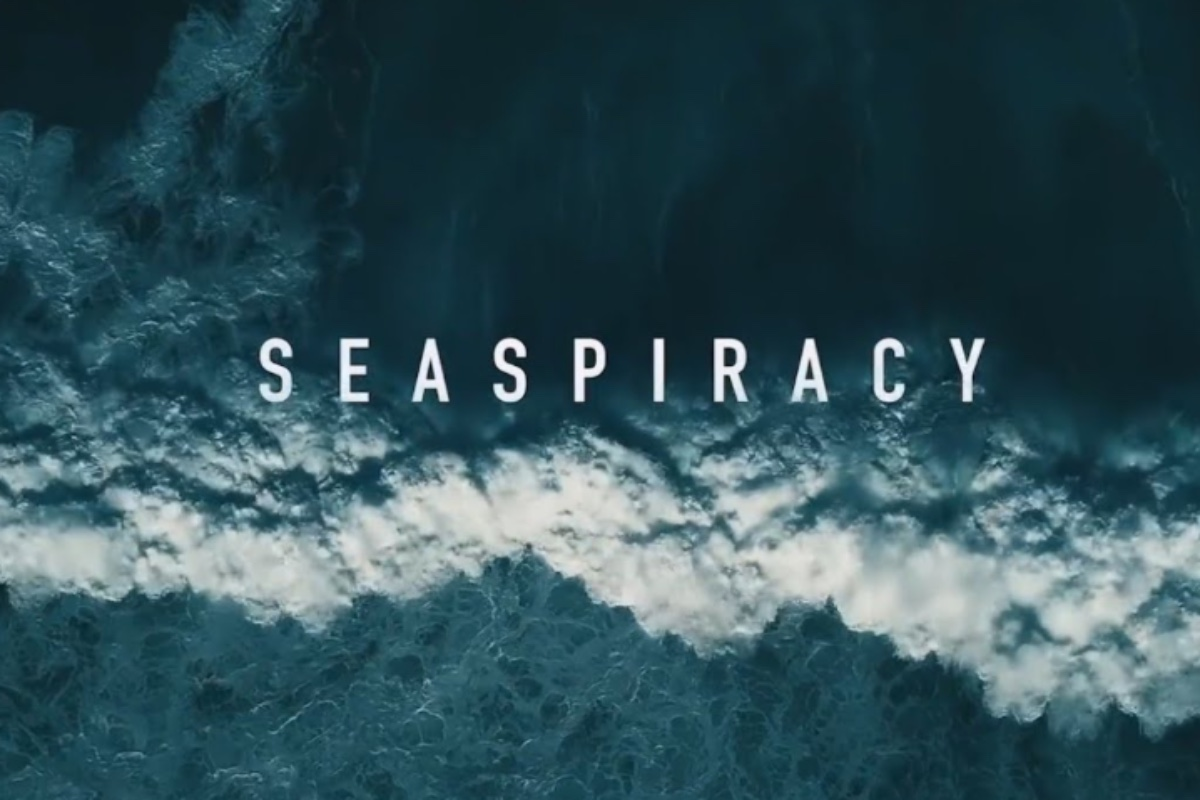 This image shows a poster for the Netflix documentary 'Seaspiracy'. In the background of the image, the ocean can be seen. There is a big wave of water crashing, just underneath the title 'seaspiracy'.
