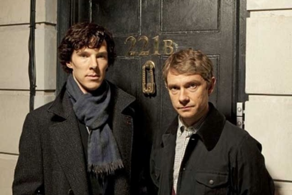 This image was taken during the first episode of Sherlock Holmes. Both the main characters are wearing black coats and staring neutrally at the camera. They are stood in front of a black door that is numbered '221B'.