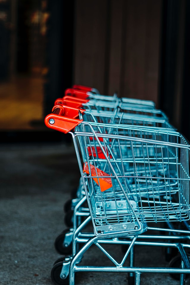In this image, four shopping trolleys are lined up against a wall side by side. All the trolleys are made from a silver metal and have orange handles.
