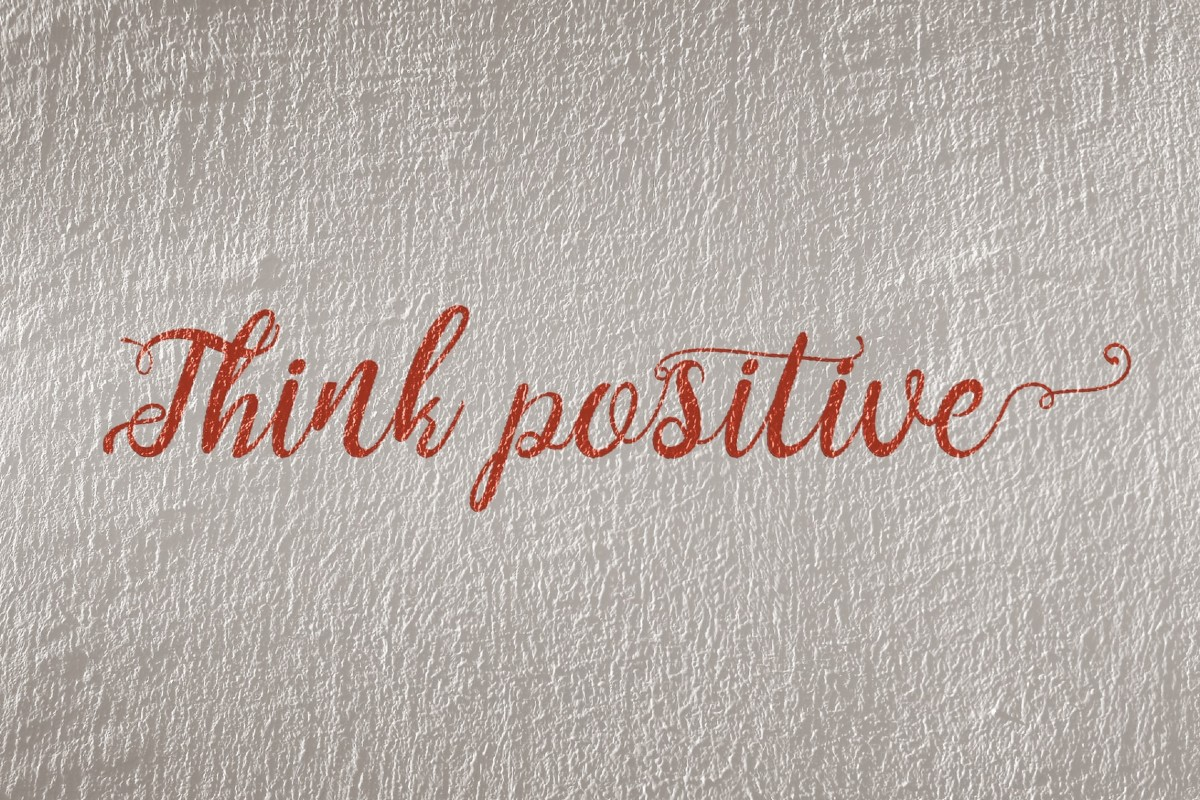 "In this image, in red writing it reads: ""Think Positive""."
