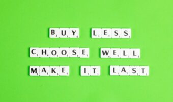"""Against a lime green background, Scrabble letter spell out """"Buy more, choose less, Make it last"""""""