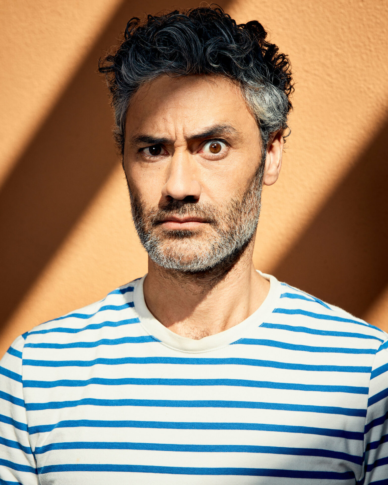 In this image, Taika Waititi is raising one eyebrow at the camera. He is earing a blue and white striped shirt and behind him is a bright orange wall.