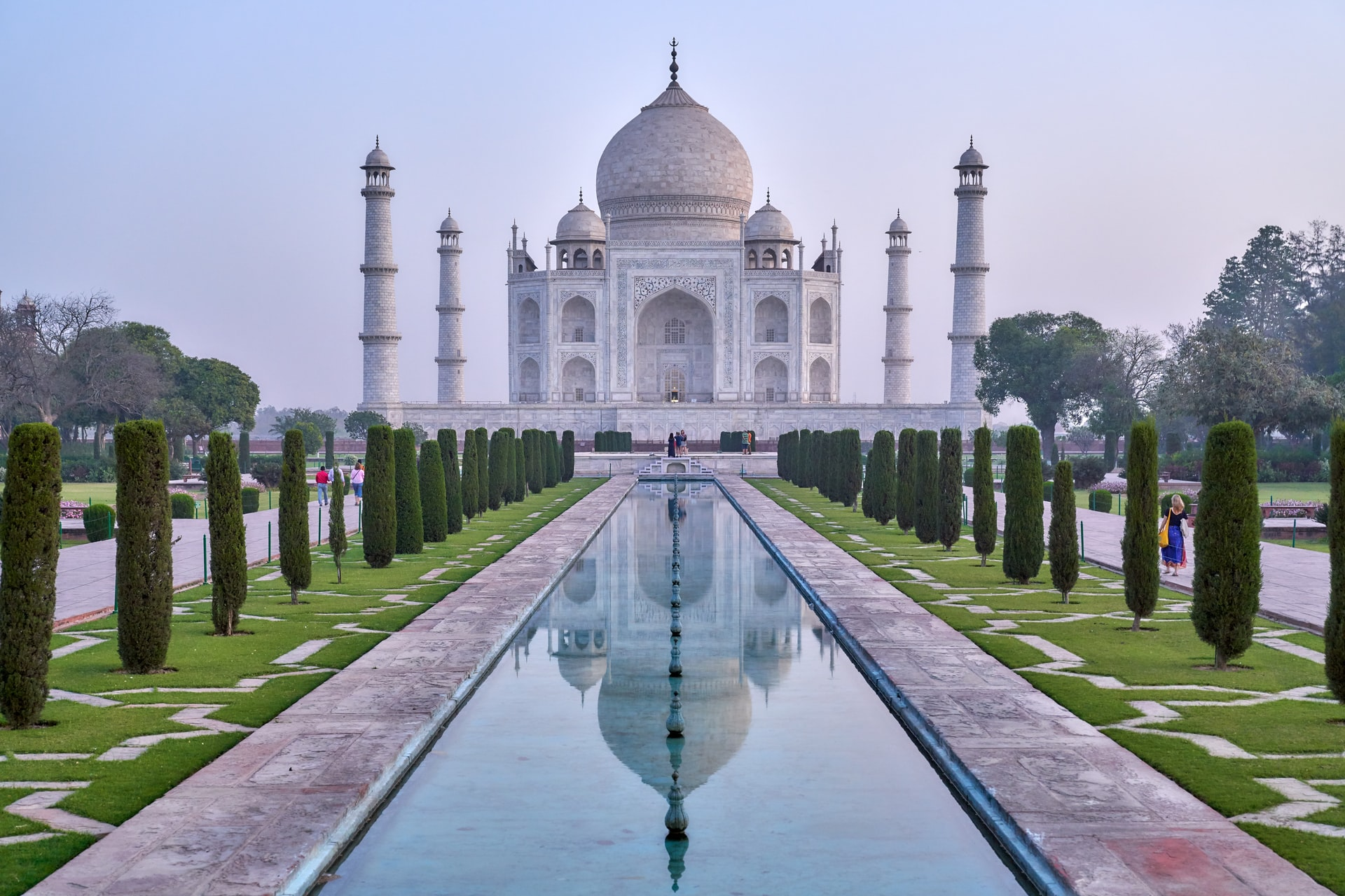 In the image, the Taj Mahal is the centrepiece in the background against a light blue sky. In front of the Taj Mahal is a long, narrow pond that is lined with trees either side.