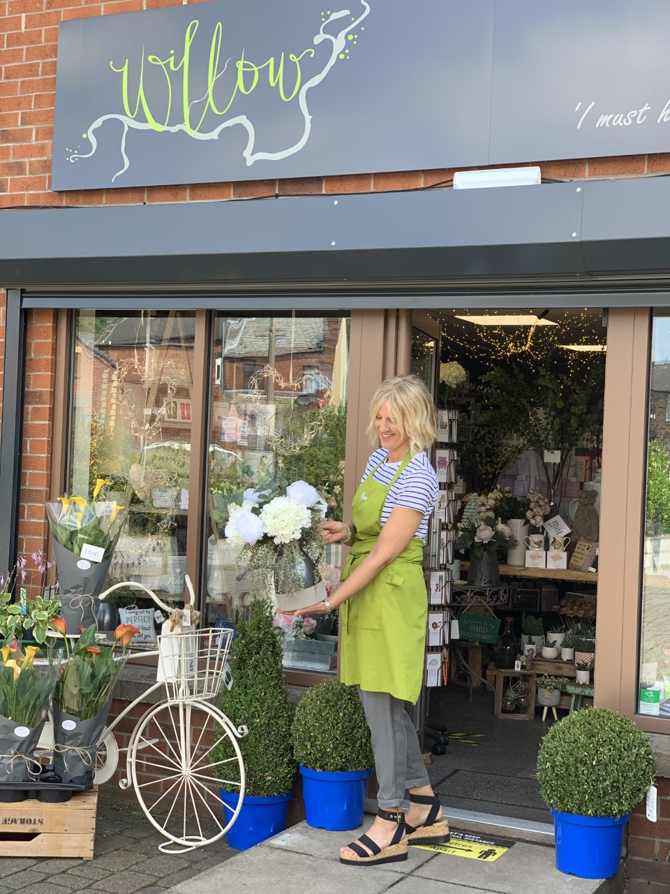 In this image, Diane is holding a white bouquet whilst stood outside of her florist. The store has a green and grey sign and a decorative bike leaning against the window.